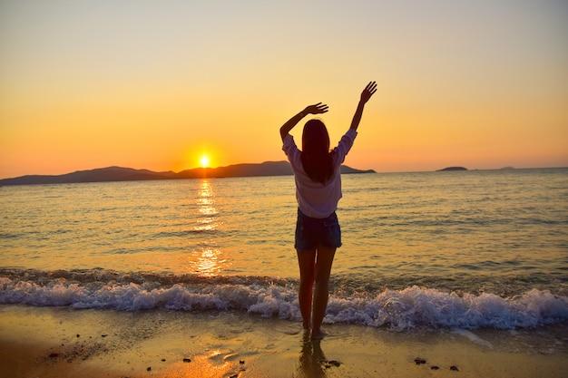 Frauen stehen am strand am meer und sonnenuntergang