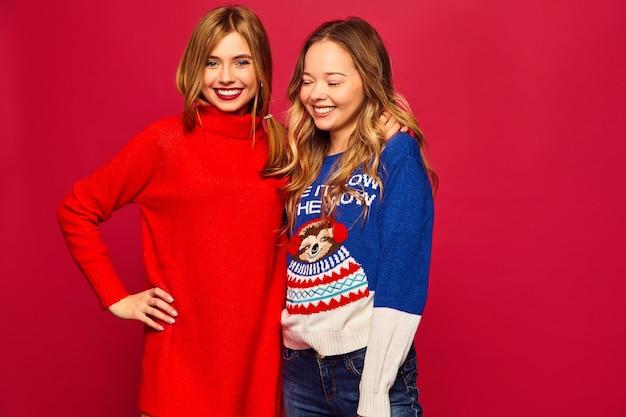 Frauen stehen in stilvollen warmen winterpullovern auf roter wand