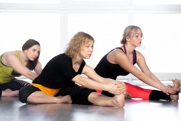 Frauen stretching im yoga-kurs