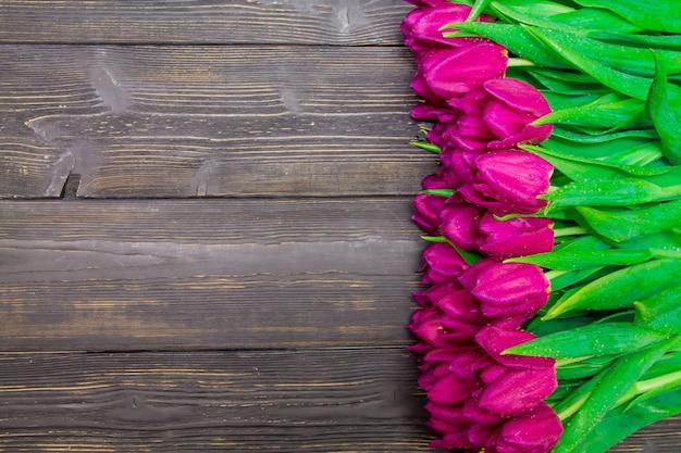 Frauen-tageskopierraum mit leuchtend rosa tulpen auf einem schwarzen hölzernen hintergrund, texturen