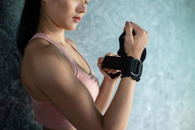 Frauen tragen armbänder, um zu trainieren und sich gegen die wand zu stellen.
