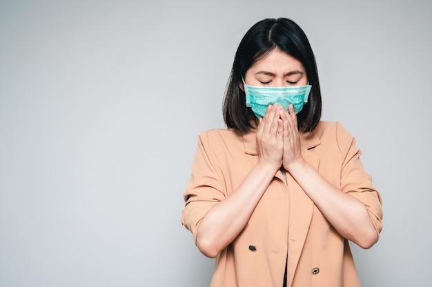 Frauen tragen eine gesichtsmaske, die niest und hustet