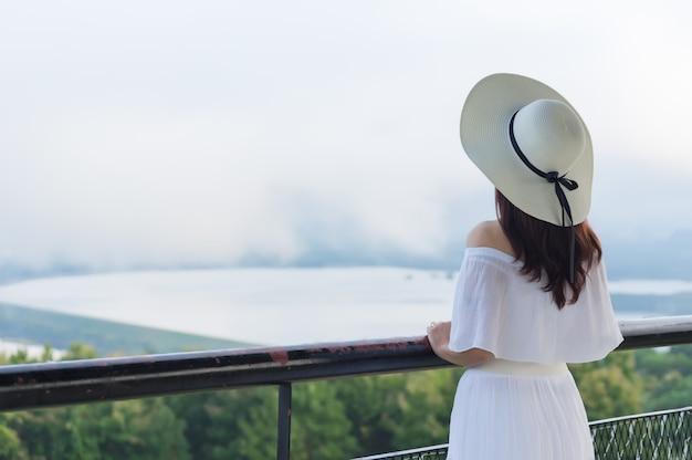 Frauen tragen einen hut mit weißer krempe stehend zurück, um die aussicht zu beobachten.