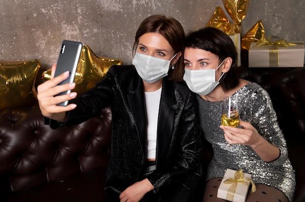 Frauen tragen gesichtsmasken, die ein selfie nehmen