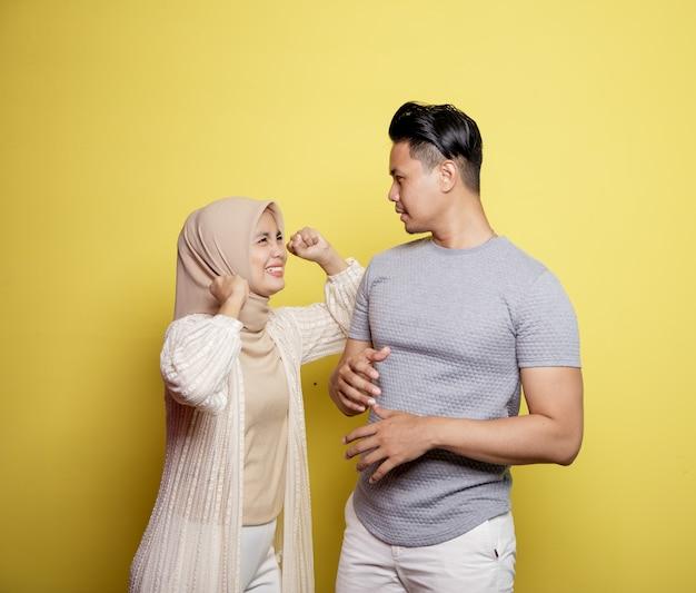 Frauen tragen hijab glücklich zu männern lächeln mit sehr glücklichen ausdrücken, die einander isoliert auf einem gelben hintergrund betrachten