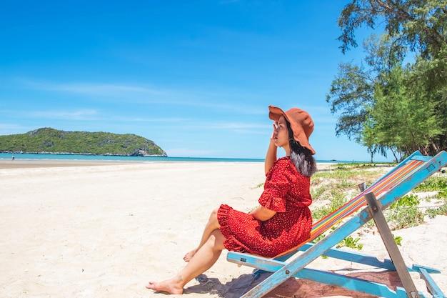 Frauen tragen hüte und sitzen im sommer auf stühlen am strand