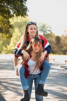 Frauen tragen ihre freundin huckepack