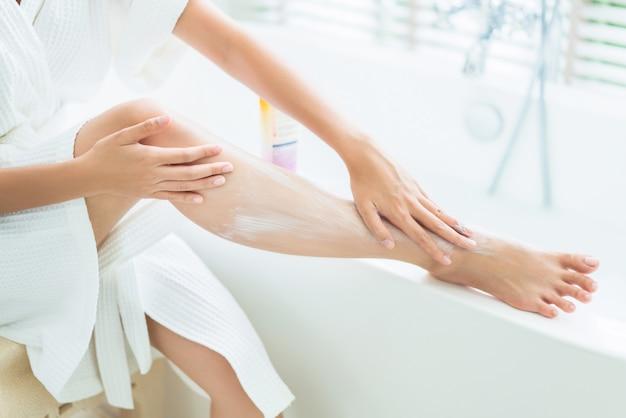 Frauen tragen lotion auf die beine auf. nach dem bad
