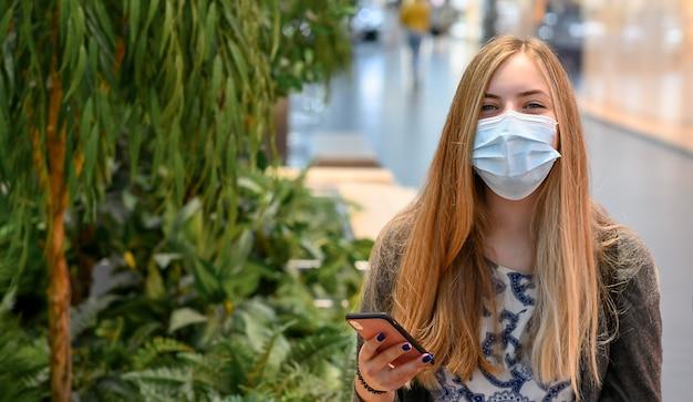 Frauen tragen masken sitzen im einkaufszentrum, mit telefonabstand sozial. lacht lächelnd.