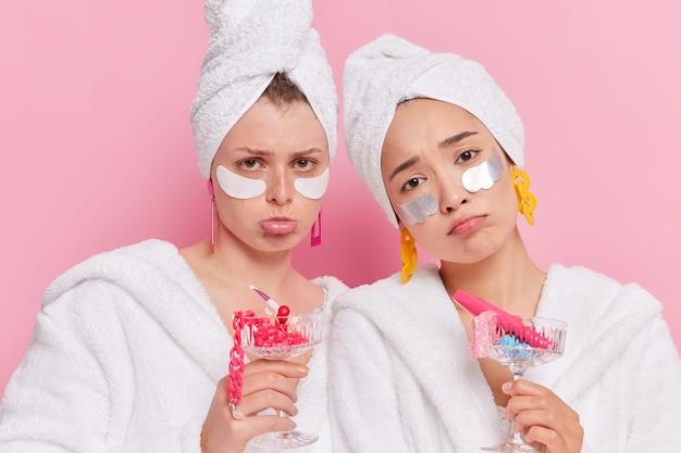 Frauen tragen schönheitspflaster auf, um die haut zu befeuchten, halten cocktailgläser voller verschiedener accessoires, die von etwas enttäuscht sind, tragen bademäntel handtuch auf köpfen isoliert auf rosa wand
