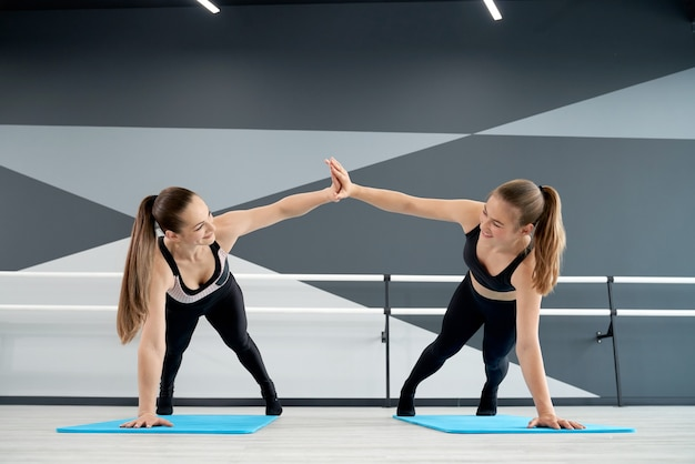Frauen trainieren auf matten in der tanzhalle