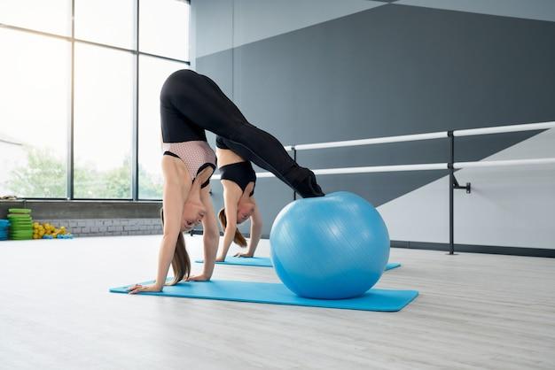 Frauen trainieren kernmuskeln mit fitnessbällen