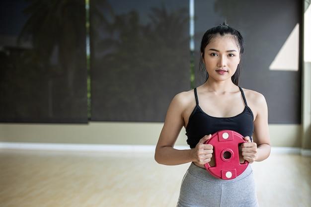 Frauen trainieren mit hantelscheiben in der brust.