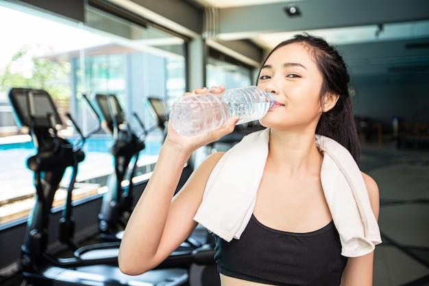 Frauen trinken nach dem training wasser aus flaschen und taschentüchern im fitnessstudio.