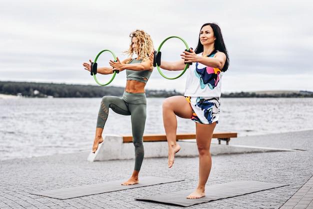 Frauen üben yoga-übungen auf einer matte mit einem speziellen sportkreis
