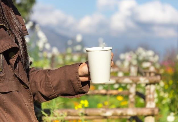 Frauen übergeben das heißhalten des kaffees im garten mit entspanntem gefühl