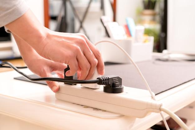 Frauen übergeben das setzen des elektrischen steckers auf stromversorgungsverbindung