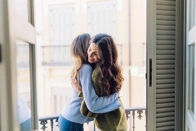 Frauen umarmen auf dem balkon