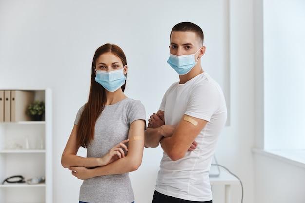 Frauen und männer mit medizinischen masken und mit klebeband auf den schultern im krankenhaus covid