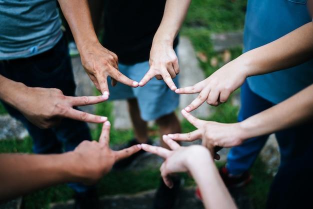 Frauen und männerfreunde machen sternform von den fingern. erfolg, freundschaftskonzept.