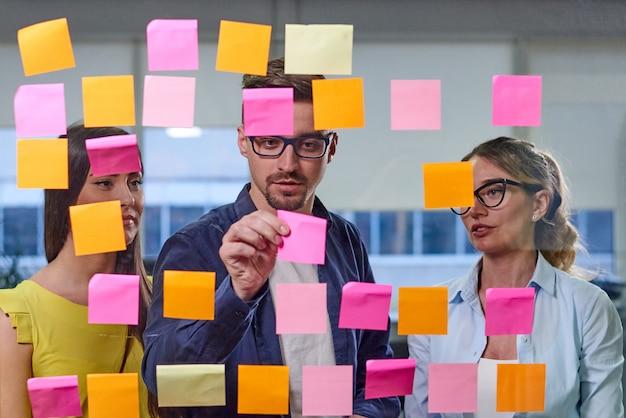 Frauen und mann, die ideen auf aufklebern besprechen
