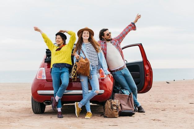 Frauen und mann mit erhobenen händen in der nähe von auto am strand