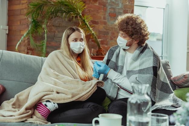 Frauen- und mannpaar in schutzmasken und handschuhen, die zu hause mit coronavirus isoliert sind