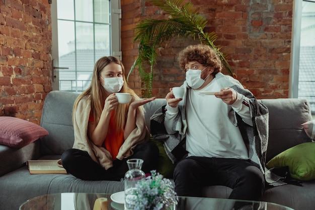 Frauen- und mannpaar in schutzmasken und handschuhen, die zu hause mit coronavirus-symptomen isoliert sind