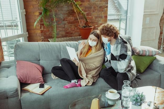Frauen- und mannpaar in schutzmasken und handschuhen, die zu hause mit coronavirusr isoliert sind