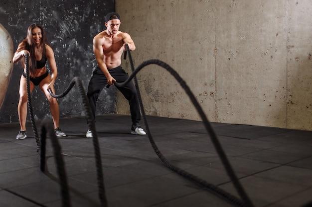Frauen- und mannpaar trainieren zusammen, indem sie das seil-training kämpfen