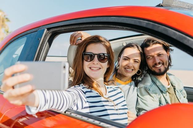 Frauen und positiver mann, die selfie auf smartphone im auto nehmen