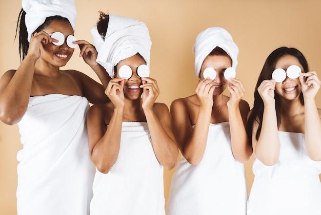 Frauen unterschiedlicher rasse mit körpertuch und make-up-reinigungstüchern, schönheit