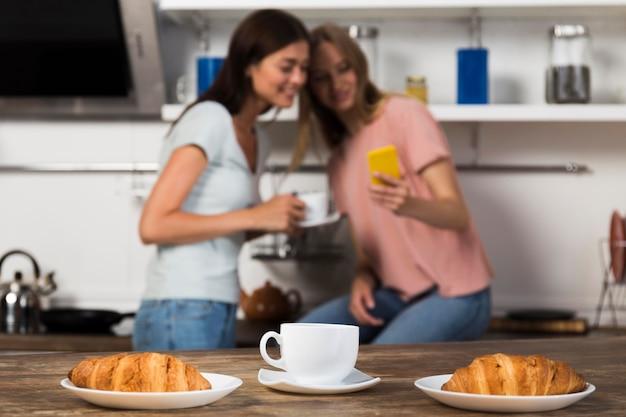 Frauen verbringen zeit zusammen zu hause mit kaffee und croissants
