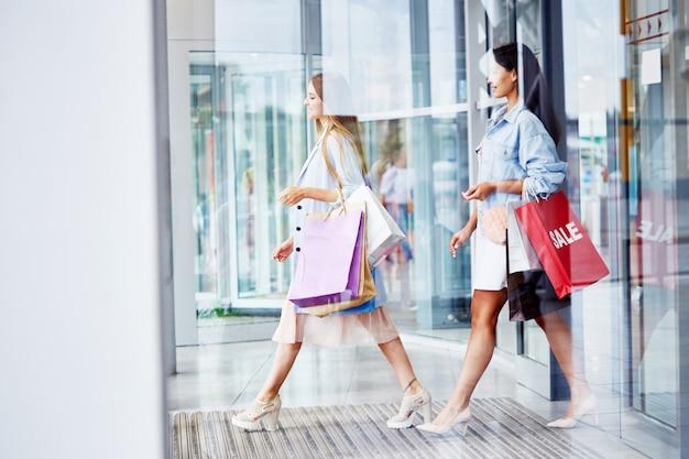 Frauen verlassen einkaufszentrum mit papiertüten