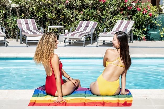 Frauen verschiedener ethnien sitzen am rand eines pools auf einer flagge des schwulen stolzes.
