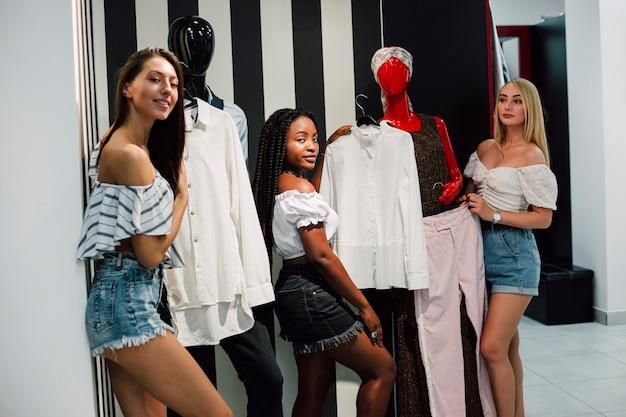 Frauen warten im fitting room, um kleider zu probieren