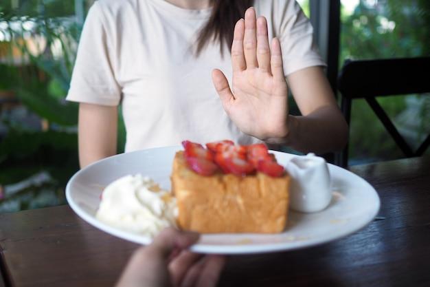 Frauen weigern sich, süßigkeiten zur gewichtsreduktion und für eine gute gesundheit zu essen.