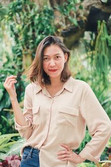 Frauen, welche die braunen hemden aufwerfen im garten tragen