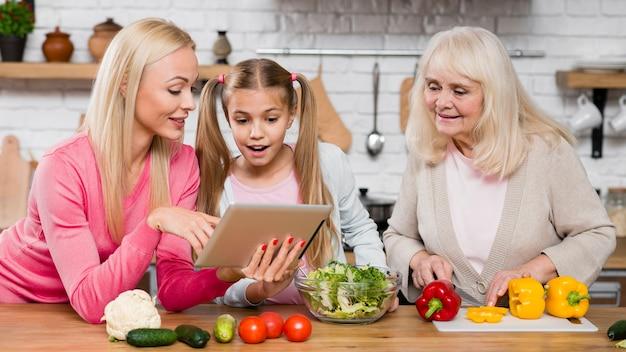 Frauen, welche die tablette in der küche betrachten