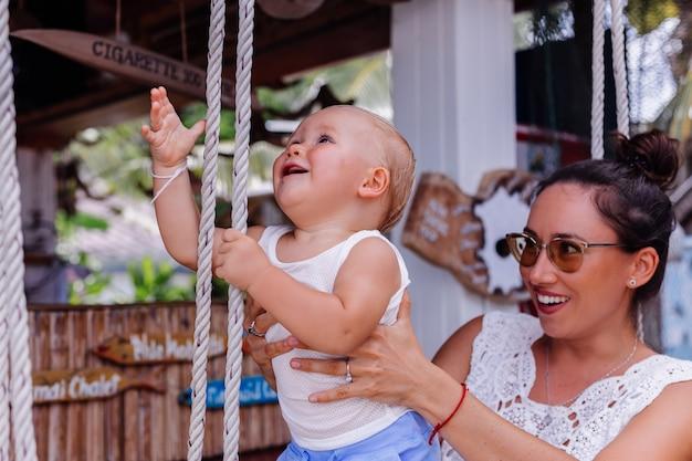 Frauen wenig lachendes kind spaß schwingen familiengarten schaukelgenuss outdoor-lifestyle menschen porträt natur kindheit zusammen park eltern freizeit tag urlaub freude glücklich