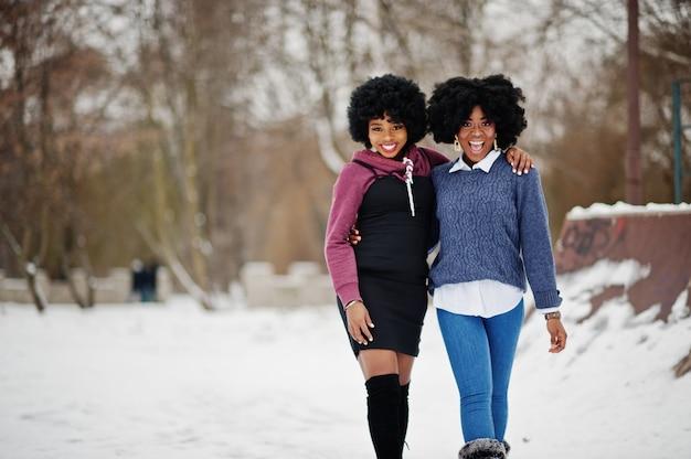 Frauenabnutzung mit zwei afroamerikanern des gelockten haares auf strickjacken warf am wintertag auf.