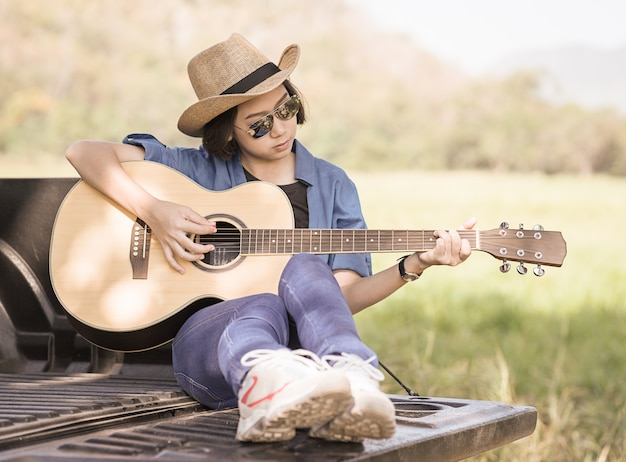 Frauenabnutzungshut und spielen der gitarre auf kleintransporter