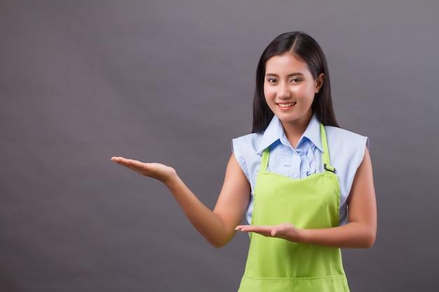 Frauenarbeiterin, die hand zeigt, etwas auf leerzeichen präsentierend