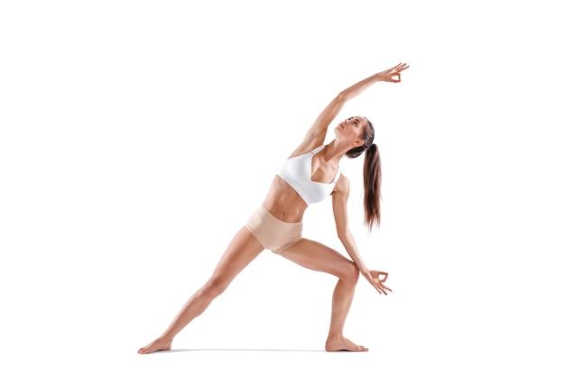Frauenarbeits-yoga-übung, porträt in voller länge, lokalisiert auf weiß. gleichgewicht und meditation, harmonie von körper und geist.
