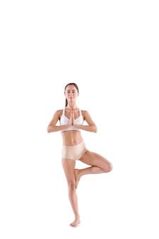 Frauenarbeits-yoga-übungsbaum-pose, porträt in voller länge, lokalisiert auf weiß. harmonie von körper und geist.