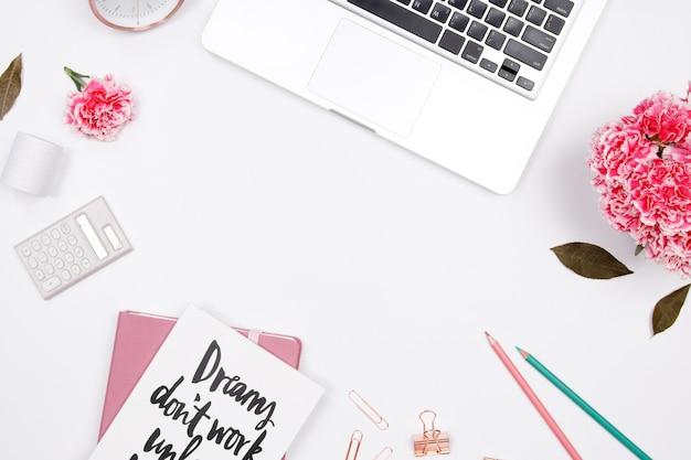 Frauenarbeitsplatz mit laptop, notizbuch, rosa gartennelkenblume, smartphone