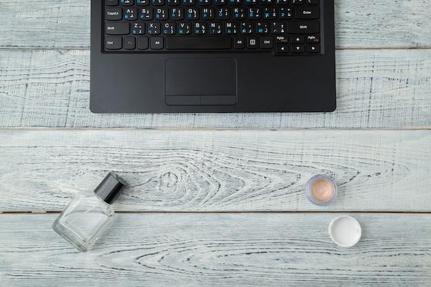Frauenarbeitsplatz mit laptop, parfüm und kosmetik