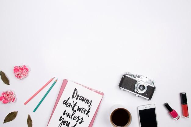 Frauenarbeitsplatz mit notizbuch, rosa gartennelkenblume, smartphone, lippenstift