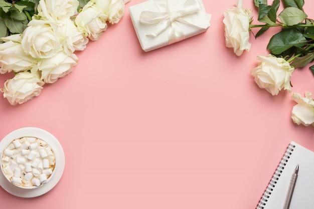 Frauenarbeitsplatz mit weißen rosen, geschenk, kaffee, notizblock, stift auf rosa. draufsicht mit kopierraum.