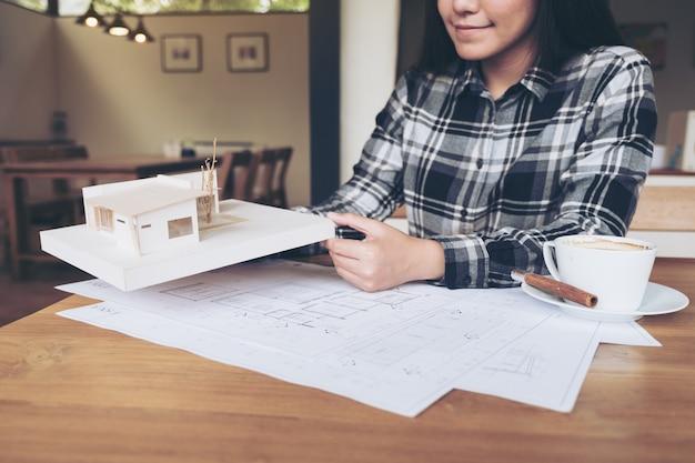Frauenarchitekt, der an einem architekturmodell mit geschäftszeichnungspapier und kaffeetasse arbeitet